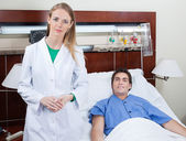 Confident female doctor with patient — Stock Photo