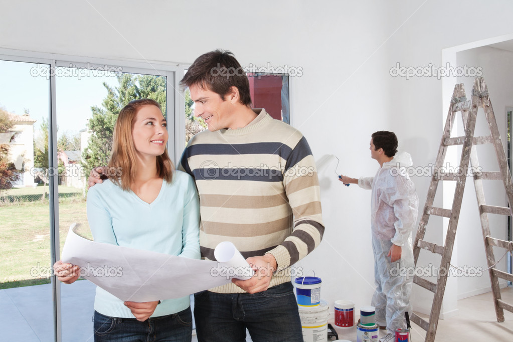 Young couple looking at each other with painter in background — Stock Photo #6556998