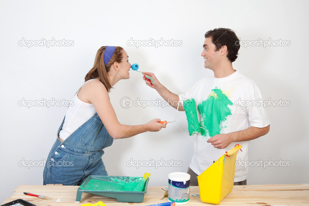 Smiling man painting his wife's nose with paint  Stock Photo #6558381