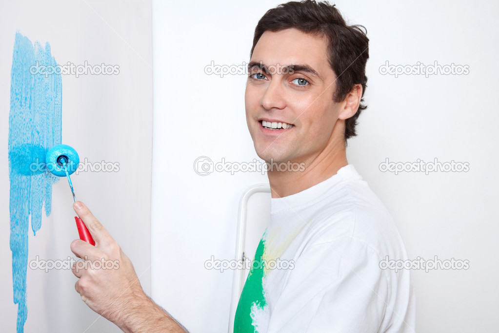 Close-up portrait of happy man painting wall with roller  Stock Photo #6558534