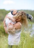 Moeder en zoon spelen in weide — Stockfoto
