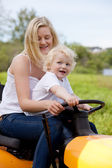 Mother Driving Tractor with Son — Stock Photo