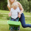 Mother and Son Pushing a Wheelbarrow — Stock Photo