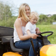 Stock Photo: Mother and Child mowing grass
