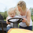 Young Boy with Mother on Garden Tractor — Stock Photo