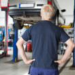 Stock Photo: Rear view mechanic looking at car