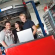 Couple in auto repair shop standing with mechanic — Stock Photo