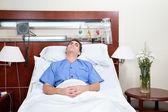Молодой пациент, лежа на кровати — Стоковое фото
