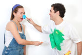 Couple playing with paint against wall — Stock Photo