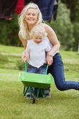 Mother and Son Pushing a Wheelbarrow — Stok fotoğraf