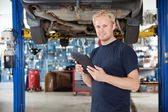 Mechanic with digital tablet — Stockfoto