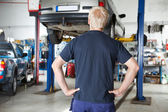Rear view mechanic looking at car — Stock Photo