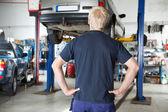 Rear view mechanic looking at car — Stock Photo