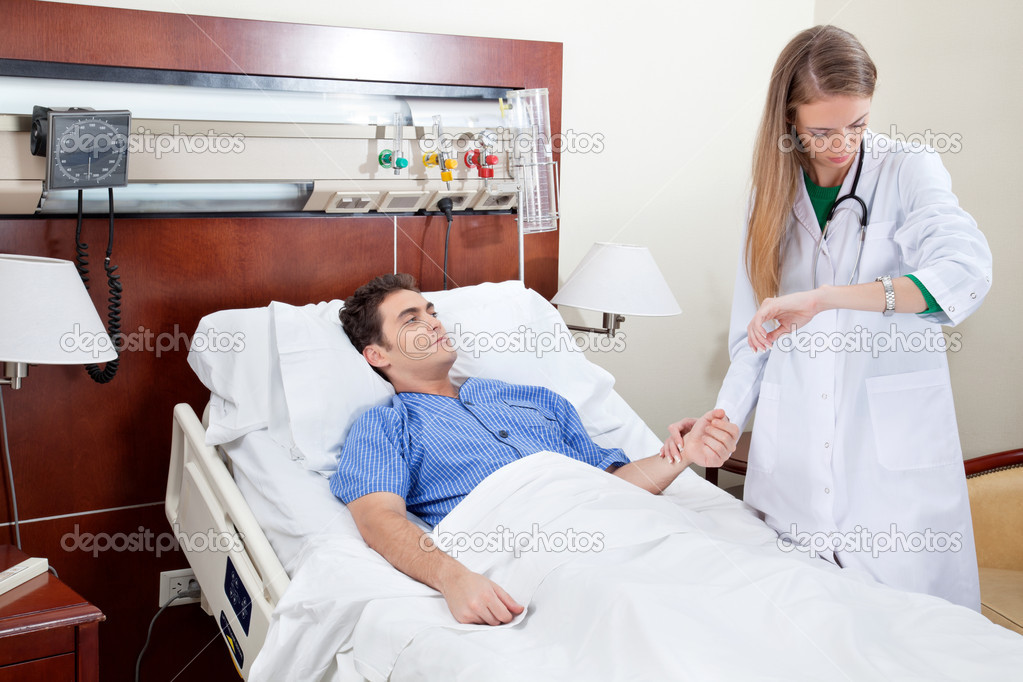Doctor checking the heartbeat of the patient in hospital  Stock Photo #6571487
