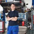 Smiling young female mechanic in garage — Stock Photo