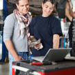 Female mechanic using laptop with client — Stock Photo