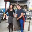 Mechanic Showing Tire to Customer — Stock Photo