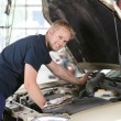 Smiling mechanic working on car - 