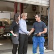 Mechanic shaking hands with client - Stock Photo