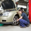 Female mechanic changing wheel — Foto Stock