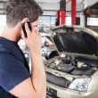 Mechanic talking on cell phone - Stok fotoraf
