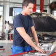 Mechanic using laptop in garage — Stock Photo