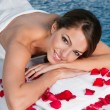 Woman with rose petals lying on bed - Stock Photo