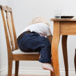 Child trying to get down from chair — Stock Photo
