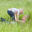 Stock Photo: Mother lying on grass and playing with son
