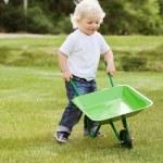 Boy pushing a wheelbarrow — Stock Photo #6585035