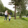 Woman and child walking in garden — Stock Photo