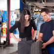 Mechanic Showing Tire to Woman Customer — Stock Photo #6586943