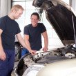 Two Mechanics Working on a Car - Stock Photo