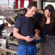 Mechanic and Customer Discussing Service Order - Stock Photo