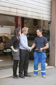 Mechanic shaking hands with client — Stock Photo