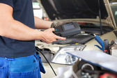 Mechanic using a Diagnostic Tool — Photo