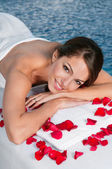 Woman with rose petals lying on bed — Stock Photo