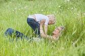 Madre sdraiato sull'erba e giocare con il figlio — Foto Stock