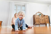 Baby crawling with mother in the background — Stock Photo