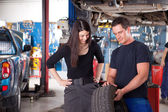 Mechanic Showing Tire to Woman Customer — Foto Stock