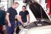 Due meccanici che lavorano su un auto — Foto Stock