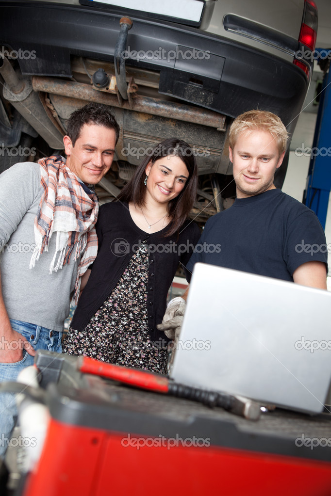 A couple with their car in repair at a mechanic shop, being shown a repair service order on a laptop — Stock Photo #6587572