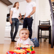 Stock Photo: Baby Playing on Floor with Parents in Background