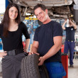 Customer with Mechanic and Tire - Stock Photo