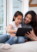 Happy Mother and Daughter with Digital Tablet — Stock Photo