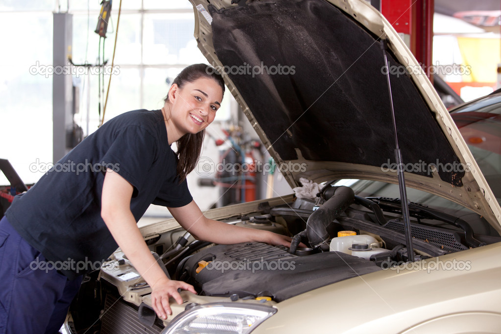 Portrait of a happy mechanic woman working on a car in an auto repair shop — Stock Photo #6605330