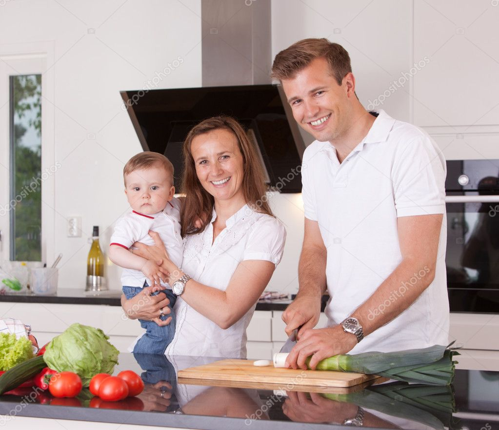 A happy family cutting vegetables in a kitchen, looking at the camera — Stock Photo #6609212