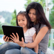 Stock Photo: Mother and girl with E-book