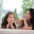 Mother and daughter on couch laughing — Stock Photo