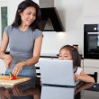 Mother and daughter with laptop in kitchen - Stock Photo